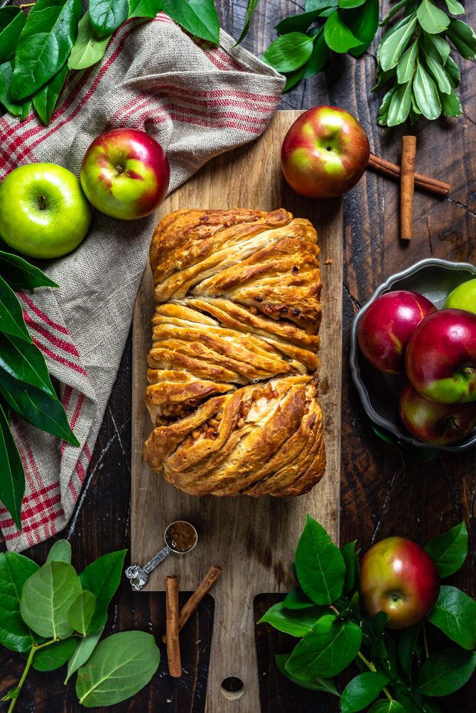 Apple Fritter Pull-Apart Bread on a serving board surrounded by apples and cinnamon sticks.