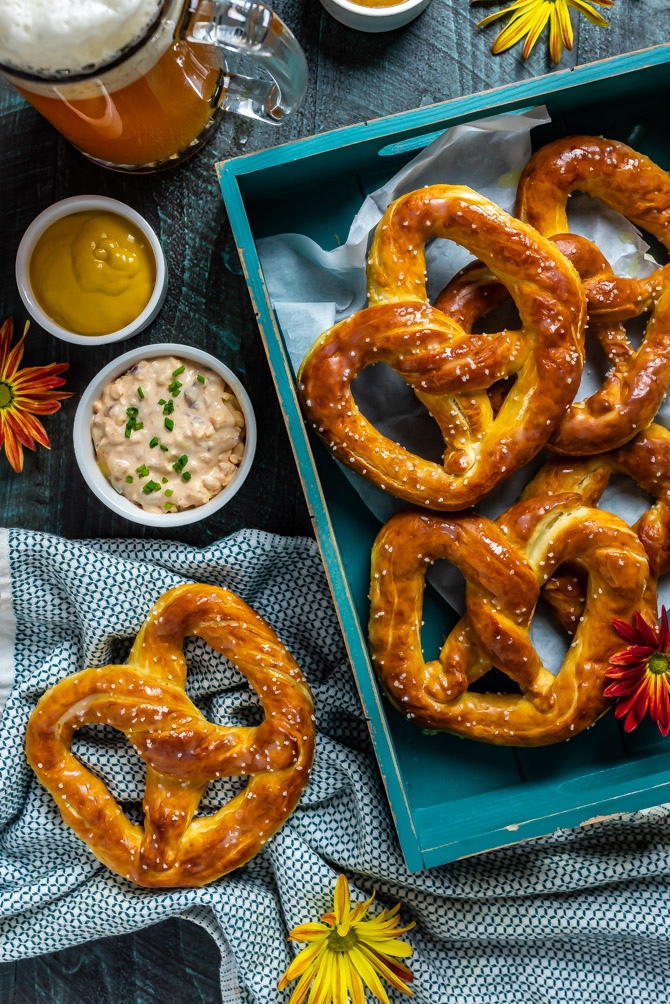 An overhead shot of Homemade Mall-Style Soft Pretzels on a blue background with assorted dips.
