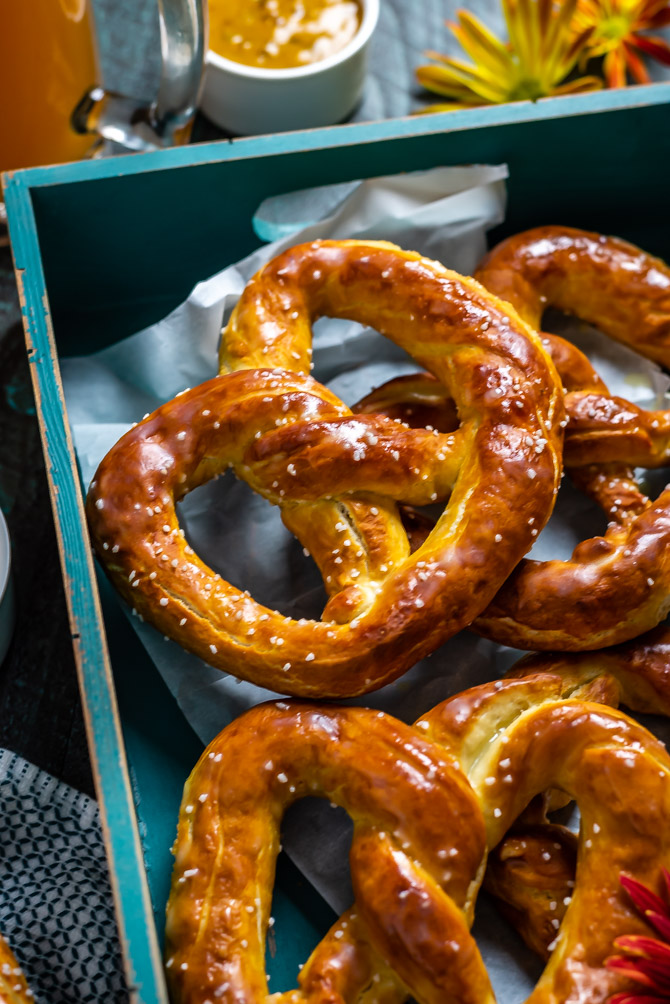 A close up shot of Homemade Mall-Style Soft Pretzels sitting on a blue wooden serving tray.