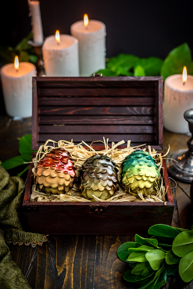 """Easter is coming! There's no better way to celebrate the holiday and the return of Game of Thrones than by making your own Chocolate Peanut Butter Dragon Eggs at home. This recipe includes a Reese's-style peanut butter filling, crunchy sliced almond """"scales"""", and a smooth chocolate coating. 