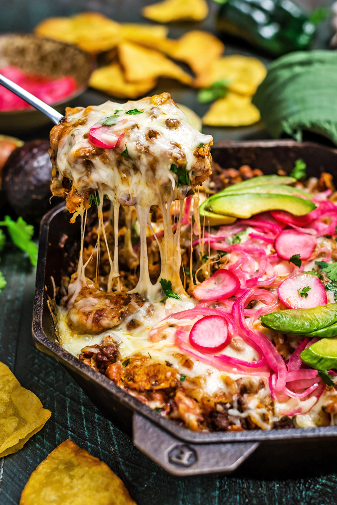 This Easy Enchilada Skillet is a one-pot meal that features from-scratch flavors. (Yup, there's no canned enchilada sauce in this one)! Loaded up with ground beef, beans, and corn tortilla strips; smothered in sauce and cheese; broiled until melty; and topped with tangy pickled onions and radishes, this dinner recipe has it all. | hostthetoast.com