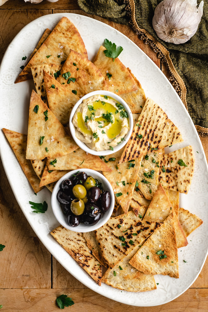 Learn how to make pita chips that crisp, golden brown, and delicious! These baked pita chips make tasty snacks on their own, or are fantastic for dunking in dips like hummus. I'll teach you how to make 4 varieties: Sea Salt, Garlic & Herb, Za'atar Seasoned, and Cinnamon Sugar!